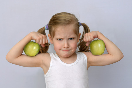 Little girl with green apples showing biceps. Stock Photo