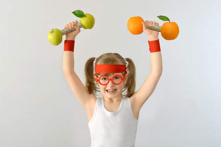 Kid, child bespectacled lifts weights from apples oranges. Stock Photo