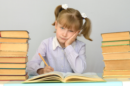 sad child surrounded by books does not want to learn