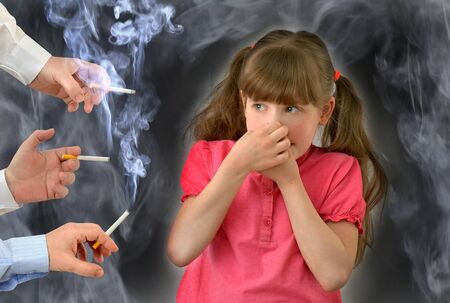 parents smoke in front of the child, kid, breathes tobacco smoke.Smoking ,bad habit, conceptual photography. 版權商用圖片