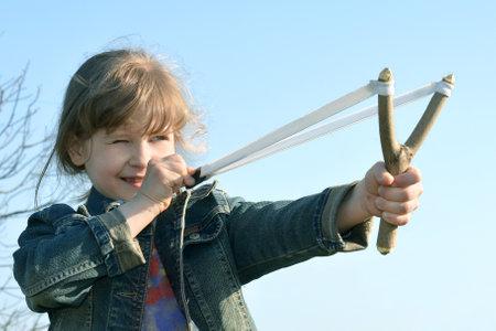 Kid, child shoots a slingshot. Conceptual photography. Foto de archivo