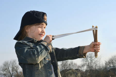 Kid, child shoots a slingshot. Conceptual photography.