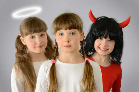behind the shoulders of the kid child are an angel and a demon teach good and evil give advice concept photography