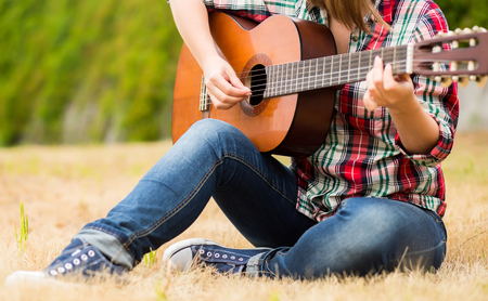 accoustic: Country girl sitting with guitar at wheat field