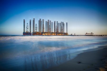 baku: beach waves with oil platform in ocean. Caspian sea offshore oil rig drilling platform off the Baku, Azerbaijan.