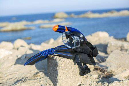 subsea: Vacation Start Here Concept, Scuba Diving Equipment On The White Sea Sand Beach with Crystal Clear Sea and Sky in Background used as Template.Blue flippers and swimming mask