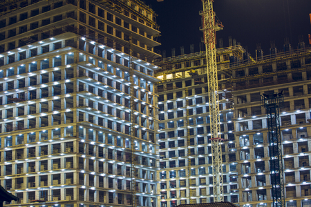 baku: Lots of tower cranes build large residential buildings at night. buildings under construction with cranes and illumination at dark night. night shot of construction equipment at building site.