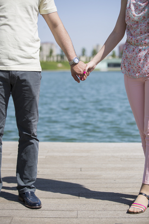 concept of love and family. the hands of lovers, men and women in beach. Young couple in love walking in the park holding hands. Archivio Fotografico