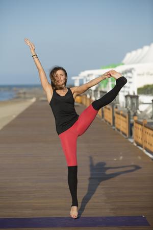 海沿いの橋の上の白いドレスでセックスの若い女性による瞑想。ビーチでヨガをやってきれいな女性。ビューの背景海でヨガの位置に座っているスポーティな女性。 写真素材 - 60355155
