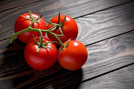 Fresh cherry tomatoes on rustic wooden background. free space on table and red vegetables of tomato on wooden cutting board.