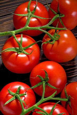 Fresh cherry tomatoes on rustic wooden background. Archivio Fotografico