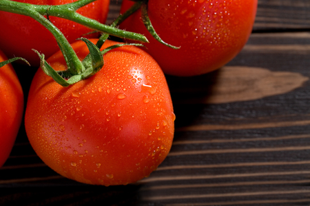 Bunch of fresh tomatoes with water drops on wooden cutting board.