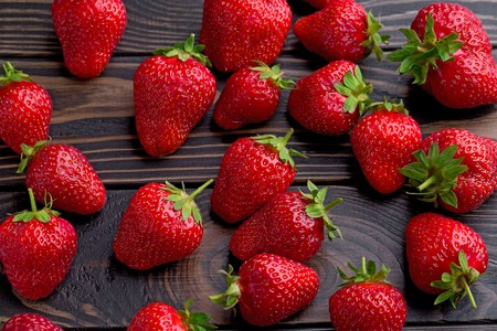 Ripe strawberries on wooden table. Fresh strawberries on wooden background.