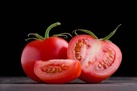 Whole red tomato with slice of tomato on wooden surface.