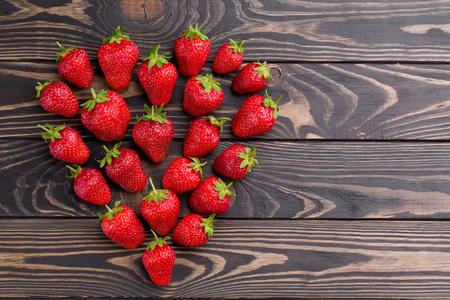 Fresh strawberries array heart shape on old wooden background. Farmer strawberries on dark wood texture in shape of heart.