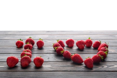 words i love you lettered with fresh organic strawberry isolated on wooden background. Love Confession. Strawberries are laid out in the letters on a background of green grass and board.