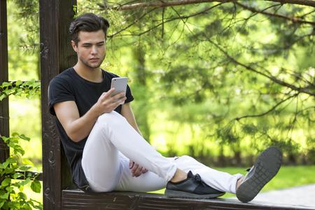 魅力的な若い男性モデルはスマート フォンでゲームをプレイします。 写真素材 - 64696200