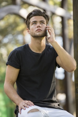 Handsome man doing a phone call, talking on cell phone, standing outdoor during daytime looking up. Archivio Fotografico