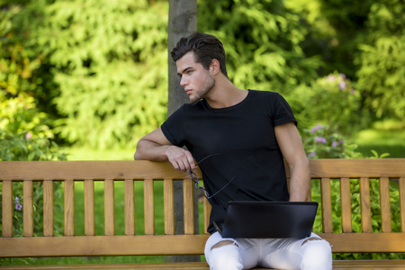 Programmer with notebook sitting in autumn park. Handsome man working on his laptop.