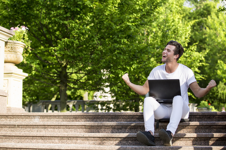 Happy cheerful handsome young man with a laptop sitting outdoors in nature, freedom and happiness concept