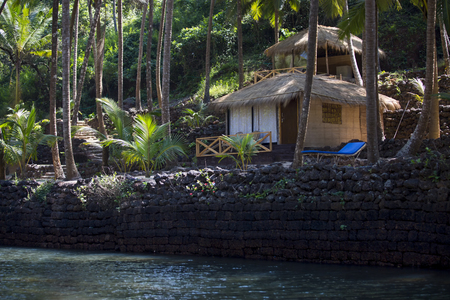 Wooden cottage with sea view in tropical resort with curved coconut palm trees. Archivio Fotografico