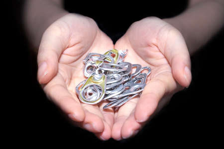 ring pull: Hand holding aluminum cap can or ring pull of can in black background Stock Photo