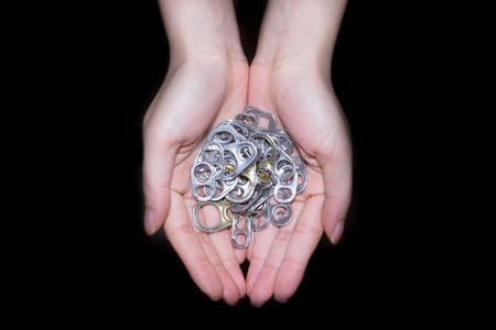amputation: Hand holding aluminum cap can or ring pull of can in black background Stock Photo