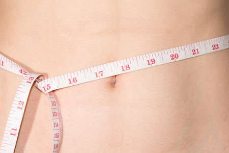 excess weight: Young slim woman measuring waist circumference, after a diet. Isolated on white background. The concept of excess weight loss and healthy eating.