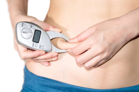 excess weight: Young slim woman check fat with fat morniter , after a diet. Isolated on white background. The concept of excess weight loss and healthy eating.