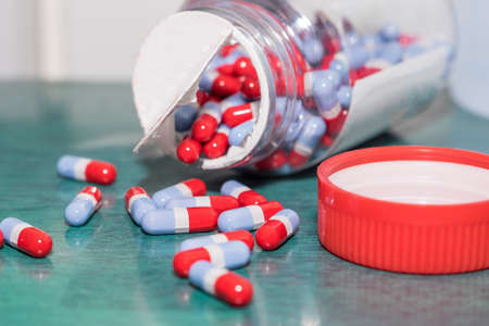 spilling: Red grey Blue pills spilling out of a plastic bottle. Stock Photo