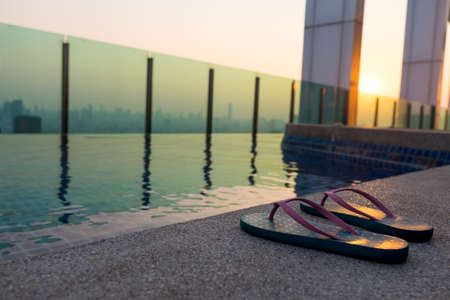 swim shoes: slippers near swimming pool at poolside sunset background Stock Photo