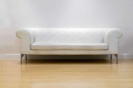 white sofa: interior, leather sofa in white room and wood floor Stock Photo