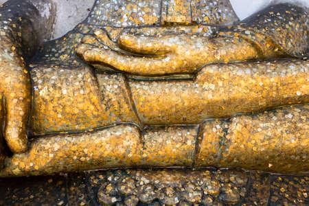 Gold leaf covered leg of big white Buddha statue