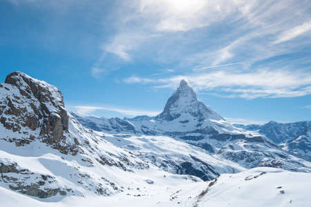 Scenic view on snowy Matterhorn peak in sunny day with blue sky and some clouds in background, Switzerland. Stockfoto