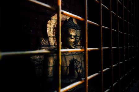 Het oude standbeeld van Boedha in de roestige ijzerkooi. Stockfoto