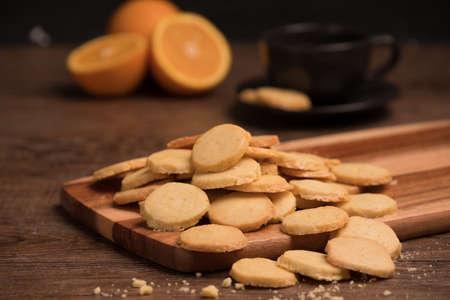 De oranje koekjes met de helft sneden sinaasappel op houten plaat, de zwarte achtergrond van de coffekop