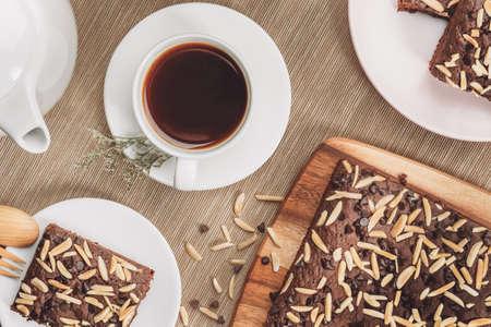 Sluit omhoog van plaat met stapel heerlijke en zachte, vierkante gesneden chocoladebrownies en extra brownies bij de pan erachter. Bovenaanzicht beeld met donkere vintage houten achtergrond.