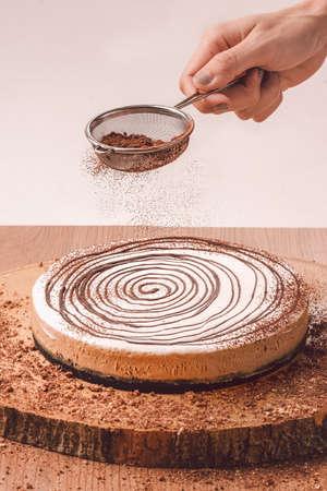Vrouwen poederende Cappuccino-kaastaart met Chocoladepoeder op houten lijst