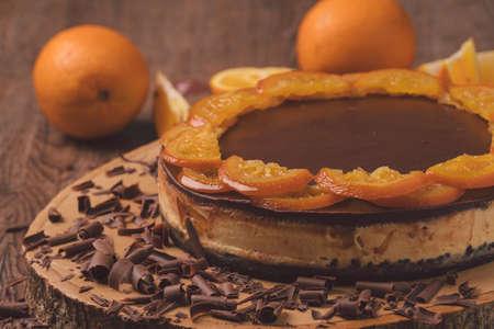 vers gebakken heerlijke oranje chocoladetaart met schijfje orance bovenop op hout.