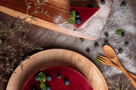 Fruitzuivel multi-coloured gelei op een plaat. De yoghurtcake van het fruit op houten achtergrond. Crème en yoghurt gebaseerd fruitvulling gegarneerd met gelei. Bosbessen, braambessen, stawberries. Rustieke voedselstijl.