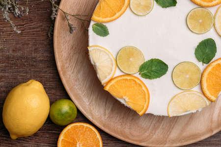 Zoet smakend zomerdessert - Lemon Cheesecake Mousse gedecoreerd met slagroom, munt, sinaasappel, limoen, citroen, uitzicht van bovenaf, topview
