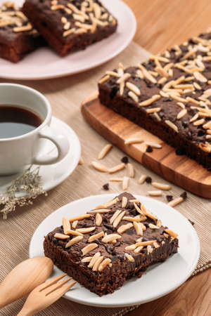 Delicious homemade assorted chewy chocolate fudge brownies with mixed nuts (almond, cashew, macadamia) on baking tray - closeup photography