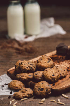Chocolate cookies , mike on  wooden table. Chocolate chip cookies shot on coffee colored cloth, closeup.