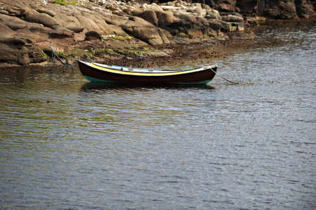 Small boat moored by rocky coast