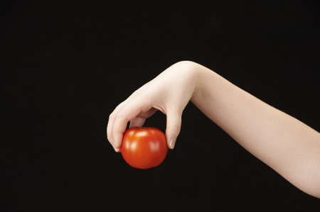 Childs hand with tomatoe  photo