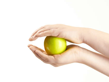 Apple sandwiched between childs hands Stock Photo