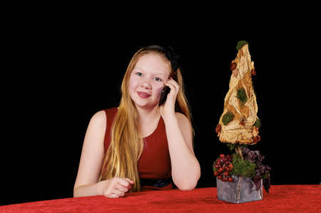 Young beautiful girl with long hair sitting by table with red tablecloth
