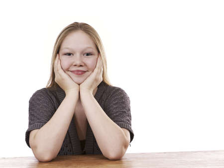 Beautiful young girl sitting by table - isolated on white background Stock Photo - 16336024