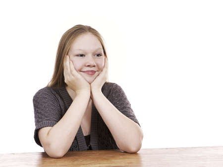 Beautiful young girl sitting by table - isolated on white background Stock Photo - 16336018