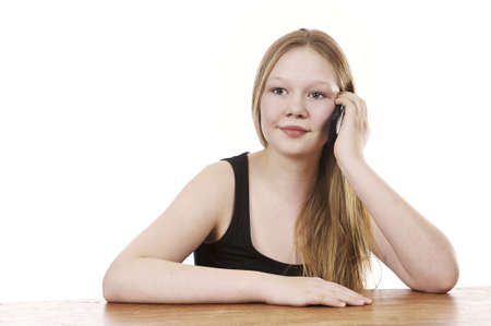 Pretty young girl sitting by table talking in cell phone - isolated on white background Stock Photo - 16336028